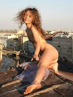 Creative pics of a gorgeous curly girl posing absolutely nude on the roof of an old building